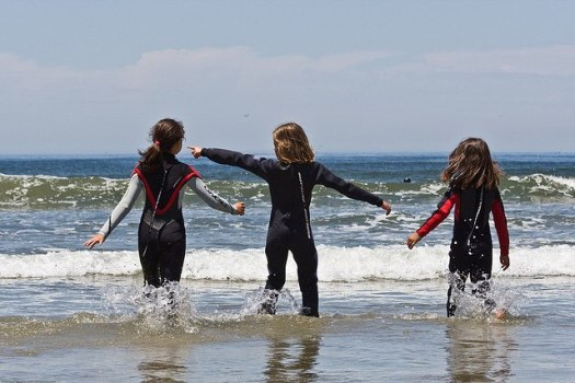 Children wearing full wetsuits into the ocean.